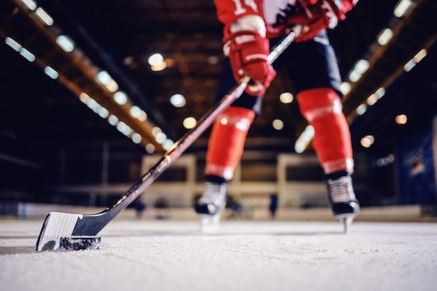 Primo piano del giocatore di hockey pattinaggio con bastone e disco.
