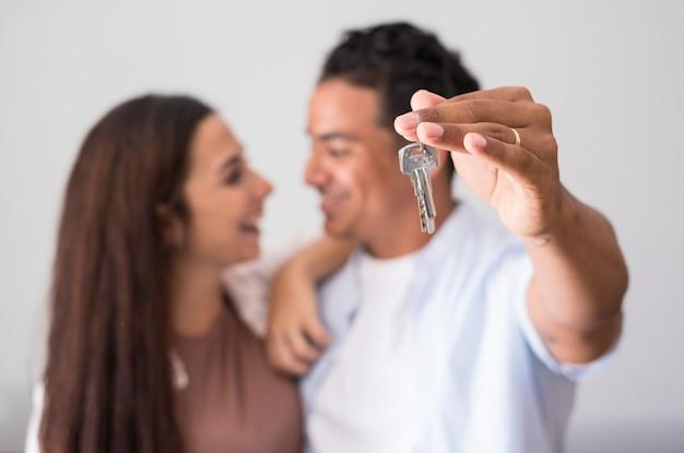 Primo piano delle chiavi di casa mostrate da una giovane coppia interrazziale felice in background concept