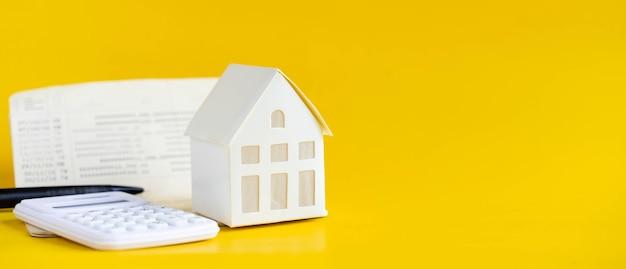 Primo piano del modello di casa e della calcolatrice e del libro dei conti bancari su sfondo esterno