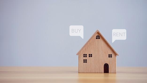 Primo piano del modello di casa con acquisto o affitto sullo sfondo del tavolo