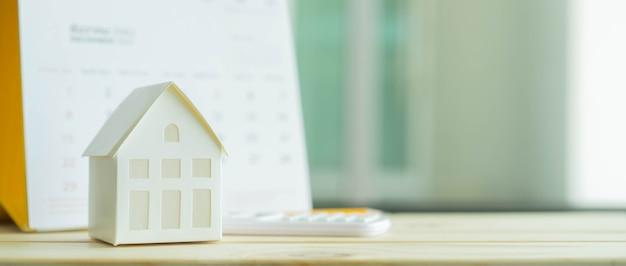 Primo piano sul modello di casa con calcolatrice e calendario sul concetto blu