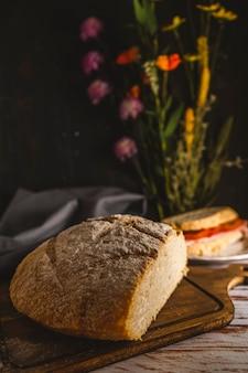 Primo piano di un ultimo taglio di pane fatto in casa con un panino fuori fuoco sullo sfondo. copia spazio. inquadratura ritratto