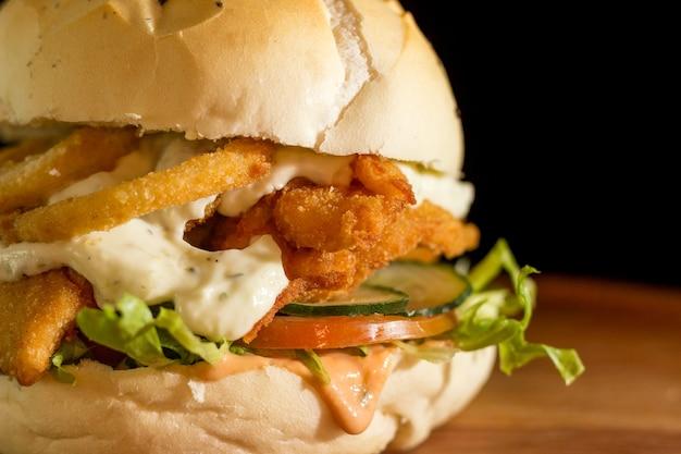 Primo piano di un hamburger di pollo fatto in casa con anelli di cipolla