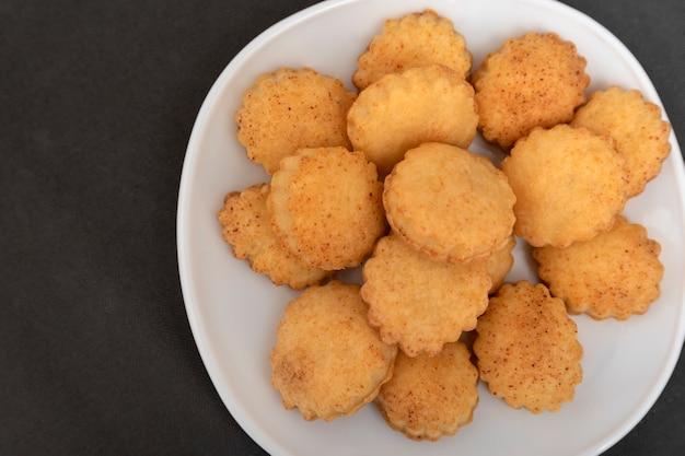 Chiuda sui biscotti fatti in casa della pasta frolla sul piatto bianco. sfondo grigio. cuocere per il tè. biscotti appetitosi.