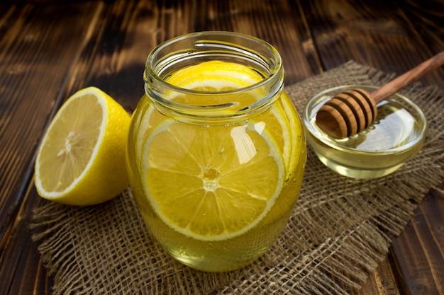 Primo piano sul miele con il limone nel barattolo di vetro