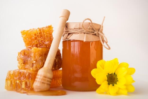 Close-up di favi, vaso con miele, dipper