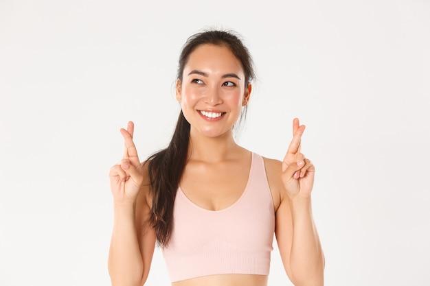 Primo piano della sportiva asiatica sorridente speranzosa che sogna di vincere la concorrenza, esprimere il desiderio e incrociare le dita per buona fortuna mentre indossa abbigliamento sportivo.