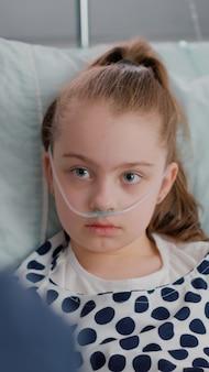 Primo piano della figlia malata ricoverata che guarda il padre mentre riposa a letto durante l'esame di recupero della malattia nella stanza d'ospedale. ragazzino che indossa il tubo nasale dell'ossigeno dopo aver subito un intervento medico