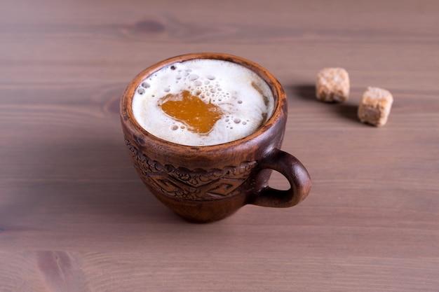 Primo piano di caffè caldo con latte in una tazza di terracotta cotta con pezzi di zucchero di canna. fondo in legno naturale.