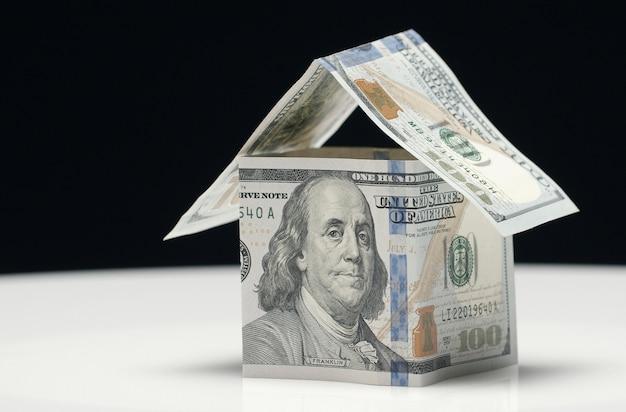 Primo piano del modello di casa fatto di banconote da 100 dollari isolato su sfondo bianco e nero