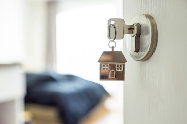 Primo piano della chiave a forma di casa su una porta