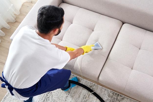 Primo piano della governante che tiene moderno aspirapolvere di lavaggio e pulizia divano sporco con detergente professionale. springclean professionale a casa concetto
