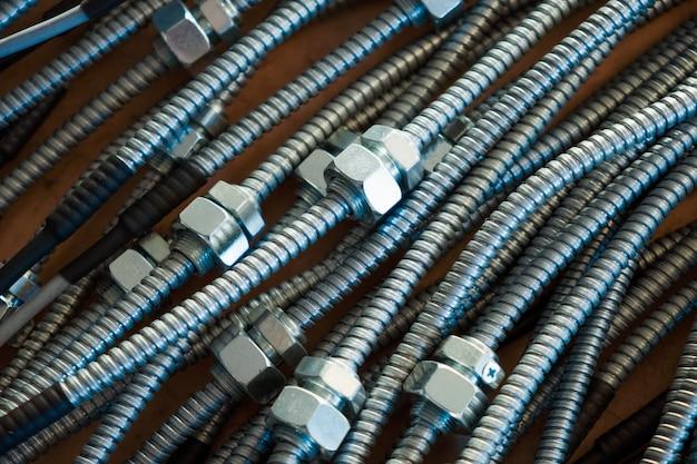 Primo piano di un enorme mazzo di tubi flessibili in metallo con dadi interconnessi in una fabbrica