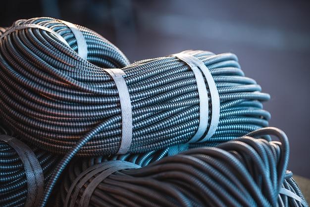 Primo piano di un enorme fascio di tubi flessibili metallici interconnessi in una fabbrica o in uno stabilimento industriale