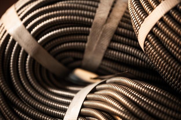 Primo piano di un enorme fascio dorato di tubi flessibili metallici interconnessi in una fabbrica o impianto. il concetto di moderna produzione militare e industriale.