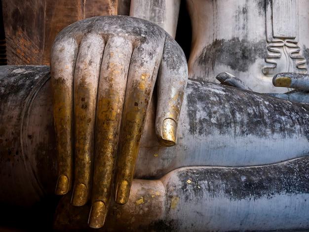 Primo piano enorme mano dell'antica statua del buddha all'interno della chiesa del tempio wat sri chum, il famoso punto di riferimento del parco storico di sukhothai, patrimonio mondiale dell'unesco in thailandia.