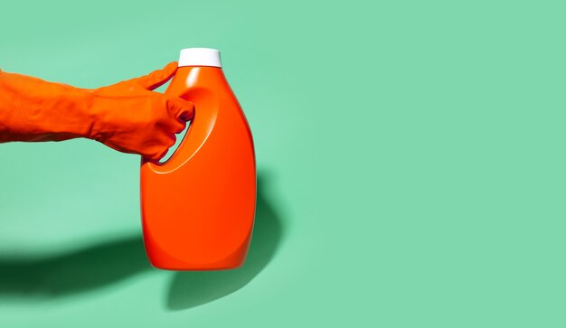 Primo piano della mano umana che indossa il guanto di pulizia, che tiene la bottiglia del detersivo di plastica sul colore di sfondo aqua menthe con lo spazio della copia e le ombre.