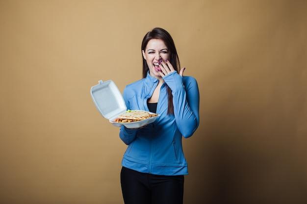 Chiuda in su della donna affamata con la bocca aperta, tenendo e mangiando grande panino. concetto di fast food