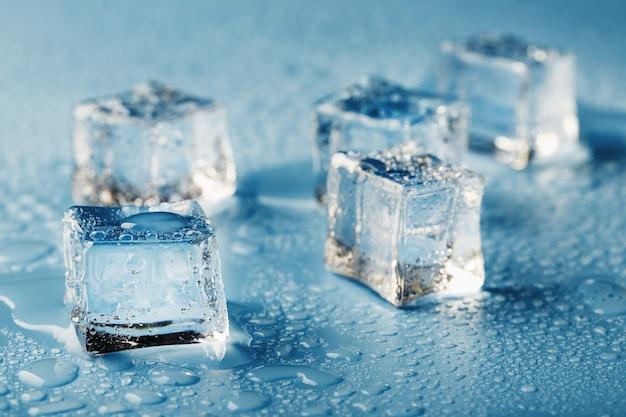 Close-up cubetti di ghiaccio con acqua di fusione gocce sparse su uno sfondo blu.