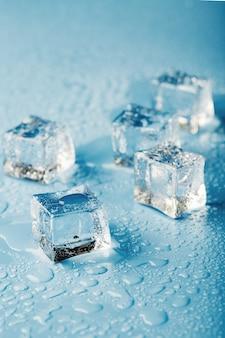 Cubetti di ghiaccio del primo piano con gocce di acqua di fusione sparse su un tavolo blu. macro. ghiaccio rinfrescante per bevande e cocktail in una giornata calda e afosa.