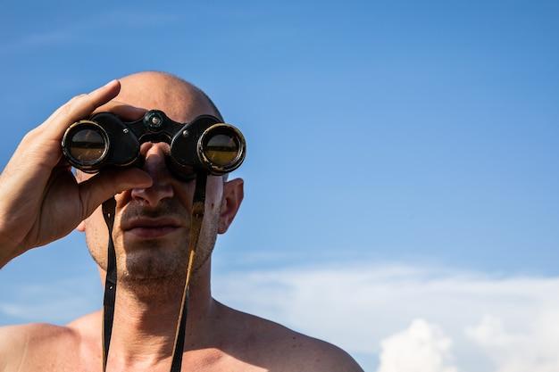 Immagine ravvicinata della mano dell'uomo calvo che tiene o guarda, guardando usando il binocolo sul cielo nuvoloso blu.