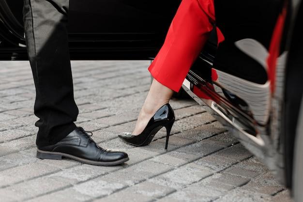 Chiuda sull'immagine di una donna di affari che esce dalla sua automobile con le scarpe dei tacchi alti.