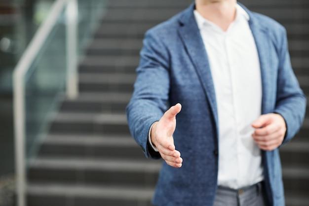 Immagine del primo piano del braccio outstreching dell'uomo d'affari per la stretta di mano