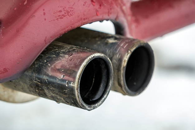 Chiuda sull'immagine di un tubo di scarico doppio dell'automobile. emissione di gas velenoso di monossido di carbonio in atmosfera, concetto di inquinamento ambientale.
