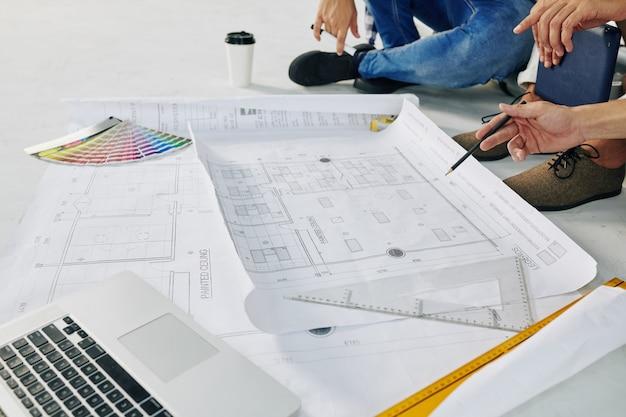 L'immagine del primo piano degli ingegneri edili che discutono del progetto della casa sta iniziando i lavori
