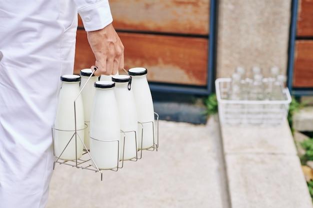 Immagine del primo piano dell'uomo di consegna che trasporta bottiglie di latte fresco alla porta d'ingresso
