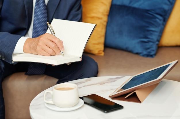 Immagine del primo piano dell'imprenditore che ha conferenza in linea con i colleghi e che prende appunti nel pianificatore