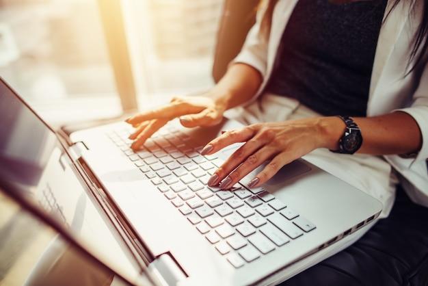 Immagine del primo piano delle mani femminili sulla tastiera. donna che lavora al computer portatile.
