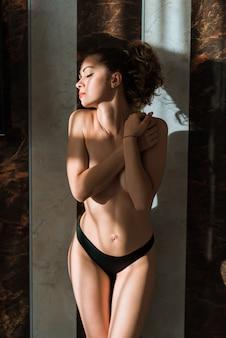 Chiuda sull'immagine della donna femminile, delle natiche e delle cosce. donna sexy in mutandine nere vicino alla finestra al chiuso in interni di lusso