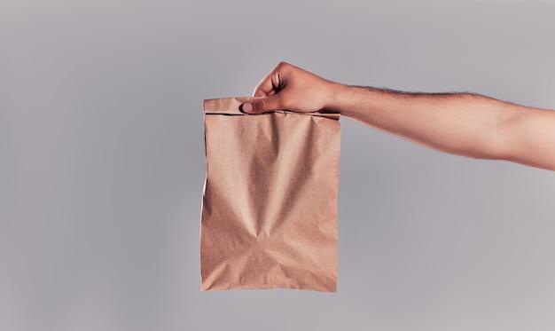 Immagine ravvicinata della mano che tiene la borsa del mestiere di carta con fastfood o cibo isolato su sfondo grigio. consegna a domicilio.
