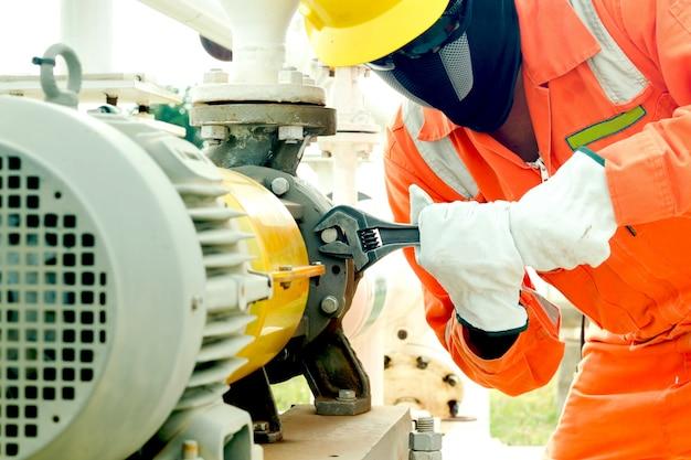 L'immagine del primo piano della riparazione umana della mano e ferma la perdita dalla chiave nel processo del petrolio e del gas