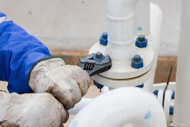 L'immagine del primo piano della riparazione umana della mano e ferma la flangia della perdita dalla chiave nel processo del petrolio e del gas