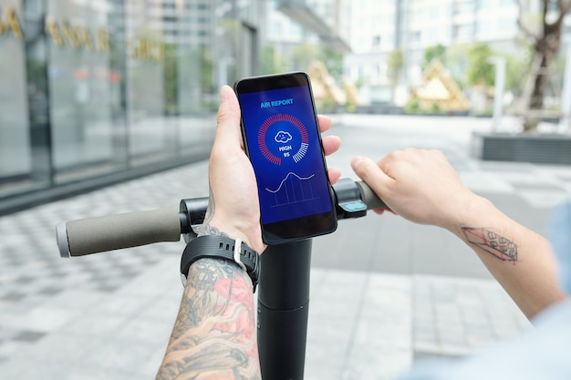 Immagine ravvicinata dell'uomo che controlla il rapporto aereo tramite applciation mobile quando si guida su uno scooter per andare al lavoro