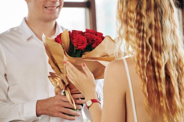 Immagine del primo piano dell'uomo che dà le rose rosse alla ragazza