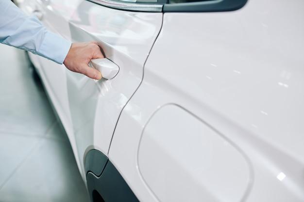 Immagine del primo piano dell'uomo che apre la porta della sua nuova automobile