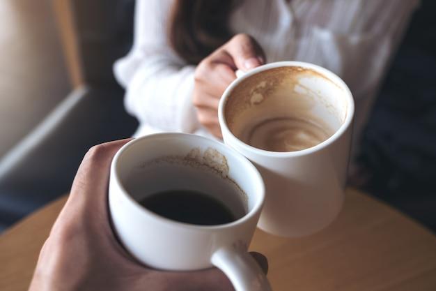 Chiuda sull'immagine di un uomo e una donna tintinnano tazze di caffè bianco nella caffetteria