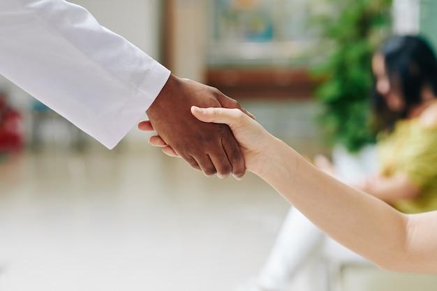 Immagine del primo piano del pediatra e del piccolo paziente che agitano le mani