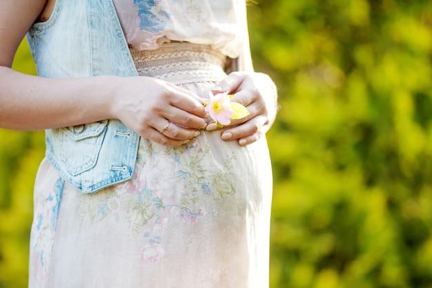 Immagine del primo piano della donna incinta che tocca la sua pancia con le mani.