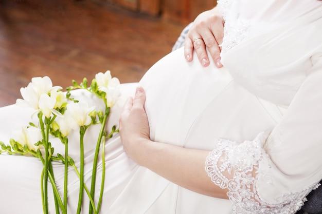 Immagine del primo piano della donna incinta che tocca la sua pancia con le mani