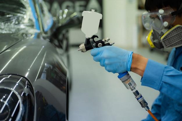 Immagine ravvicinata di verniciatura professionale per auto, messa a fuoco in primo piano.