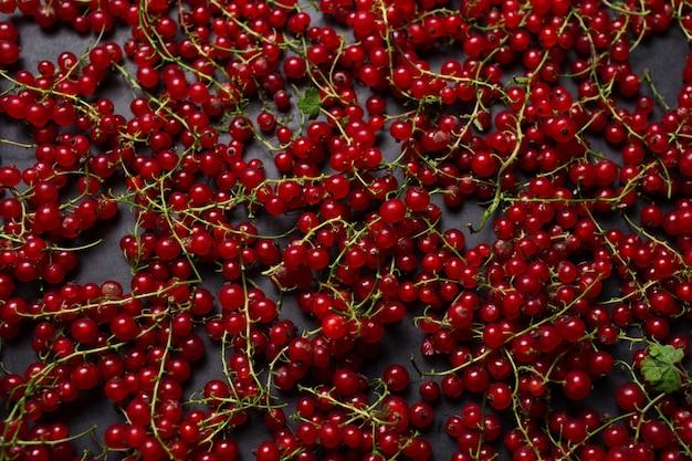 Immagine ravvicinata di ribes rosso sparsi su uno sfondo nero.