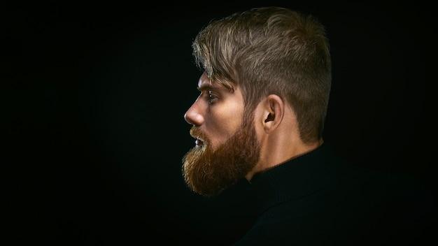 Immagine ravvicinata di un uomo barbuto serio e brutale su sfondo scuro concetto sicuro e drammatico vista laterale