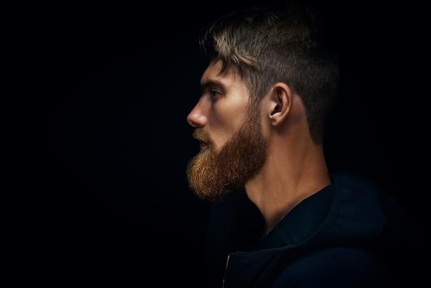 Immagine ravvicinata di un uomo barbuto brutale serio su sfondo scuro concetto sicuro e drammatico