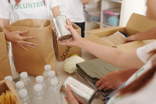 Immagine ravvicinata di volontari che imballano cibo in scatola, acqua in bottiglia e vestiti in scatole di cartone per inviarlo alle vittime dell'uragano