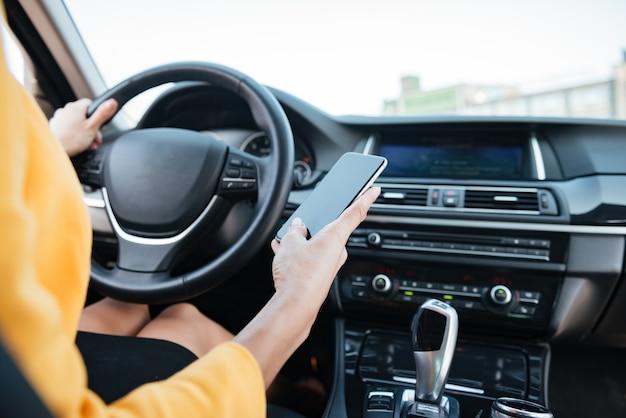 Chiuda sull'immagine con il driver femminile e lo schermo in bianco del telefono