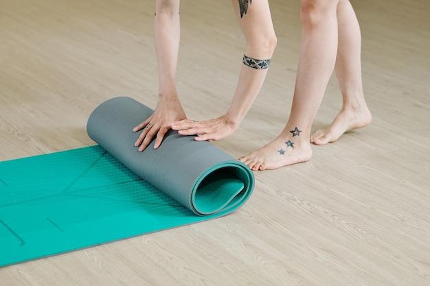 Immagine del primo piano della donna che rotola sul materassino yoga dopo l'allenamento in studio
